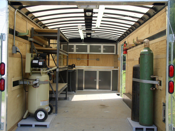 Complete trailer, air compressor, gas rack, overhead lights, E-track, workbench, shelving.